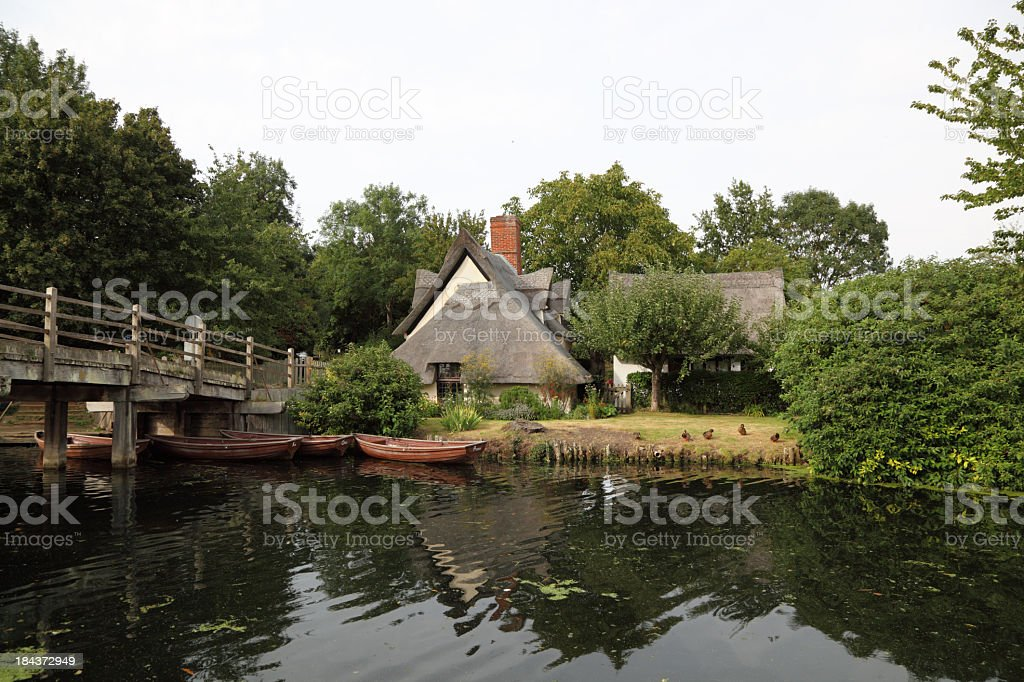 thatched english cottage with lawn by peaceful riverbank stock photo