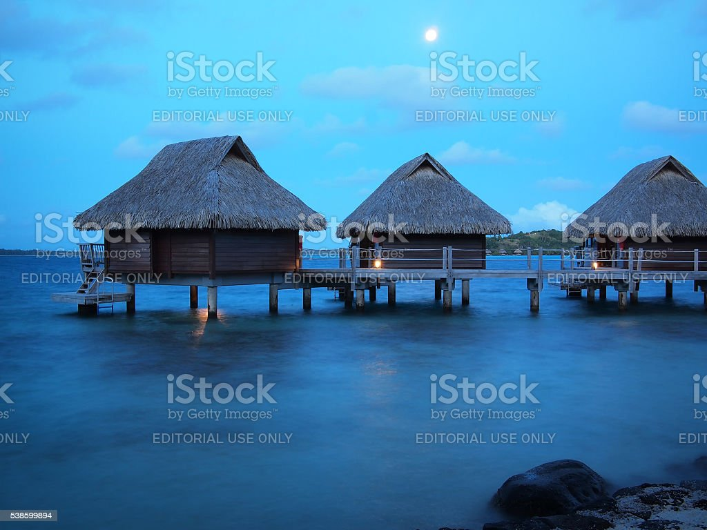 Thatched roof overwater bungalows at blue hour stock photo
