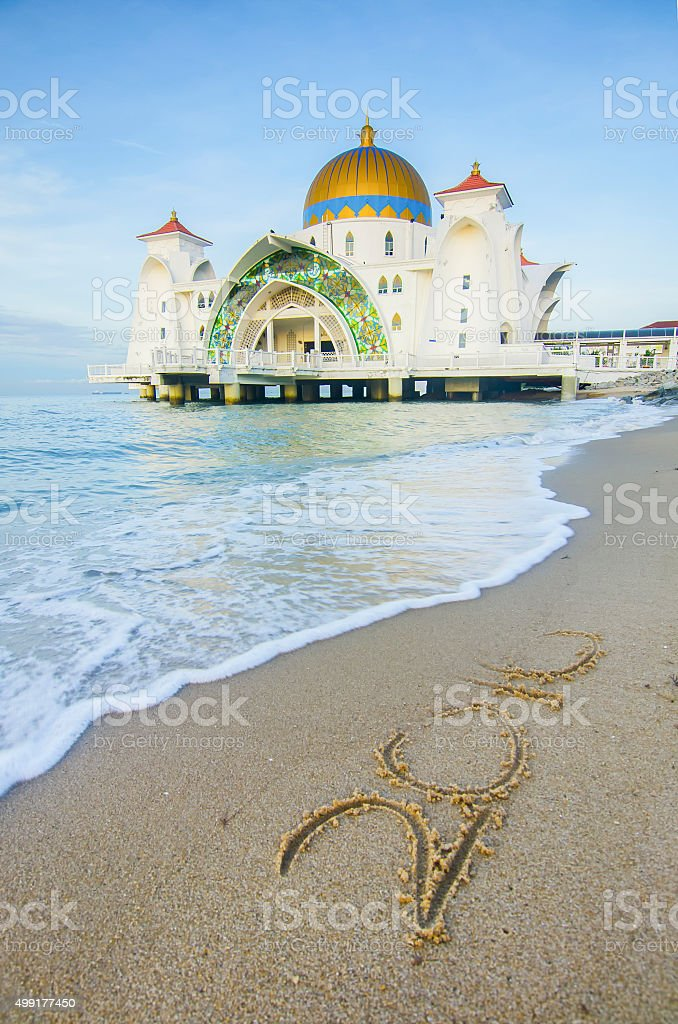 the 2016  word written on the sand Malacca Straits Mosque. stock photo