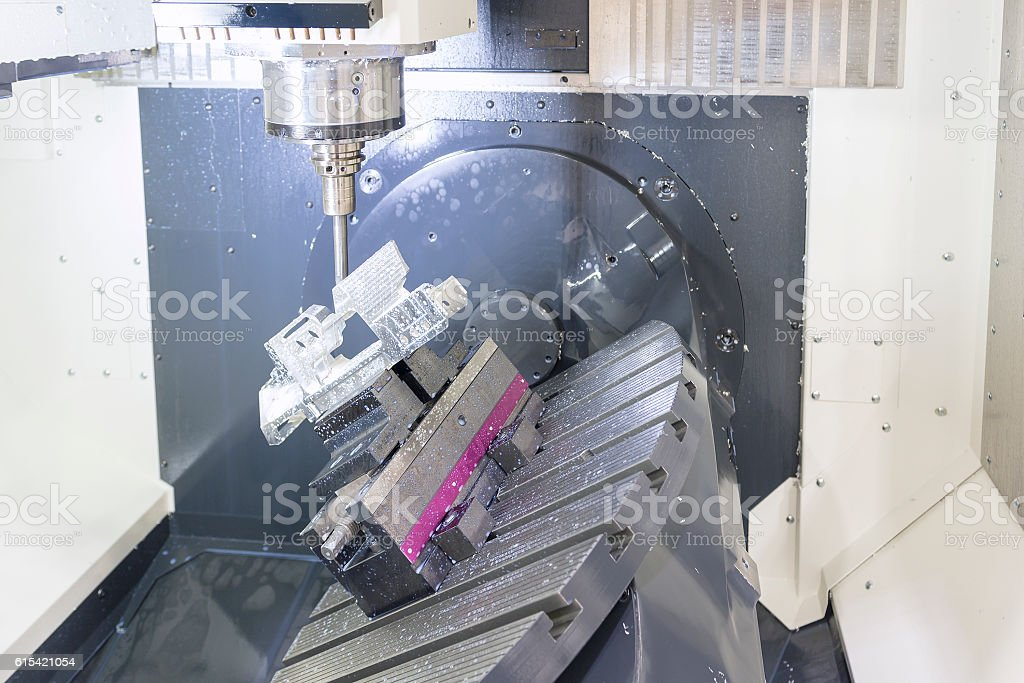 The 5-axis CNC machine while cutting the sample part stock photo