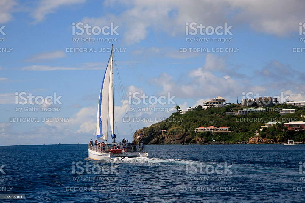 The 'Adventuress' Catamaran Sailing Past St. Thomas' Villas royalty-free stock photo