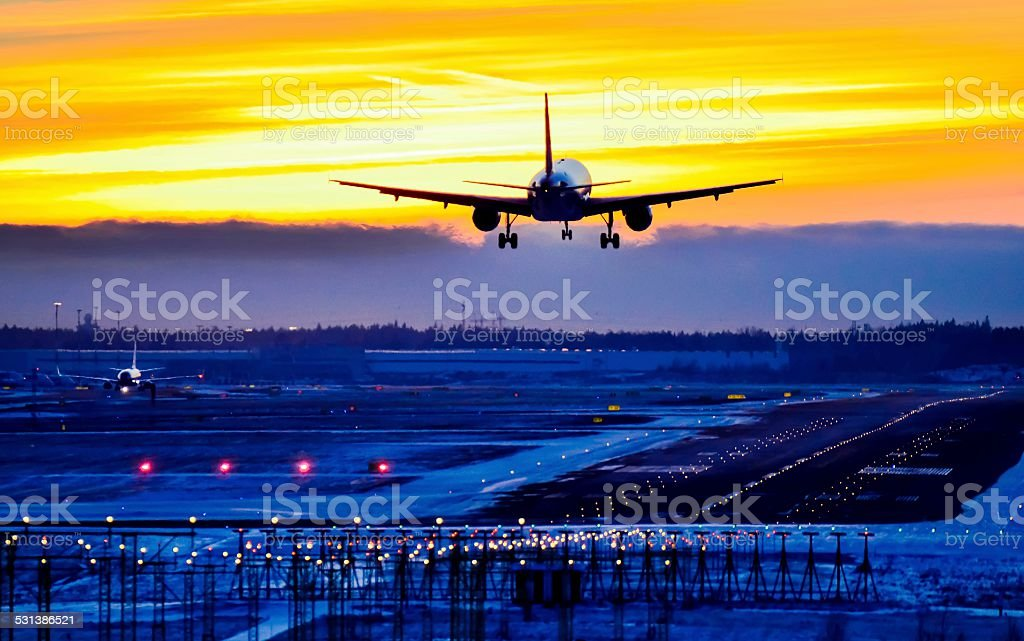 The airplane landing at the airport runway at sunset stock photo