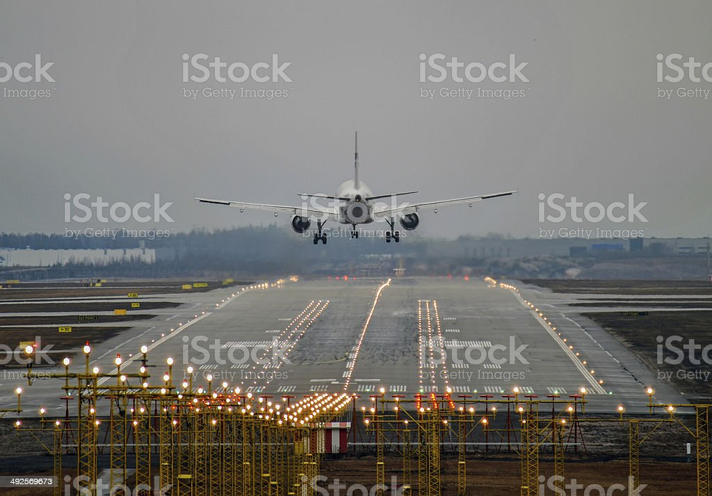The airplane lands to runway on a foggy day stock photo