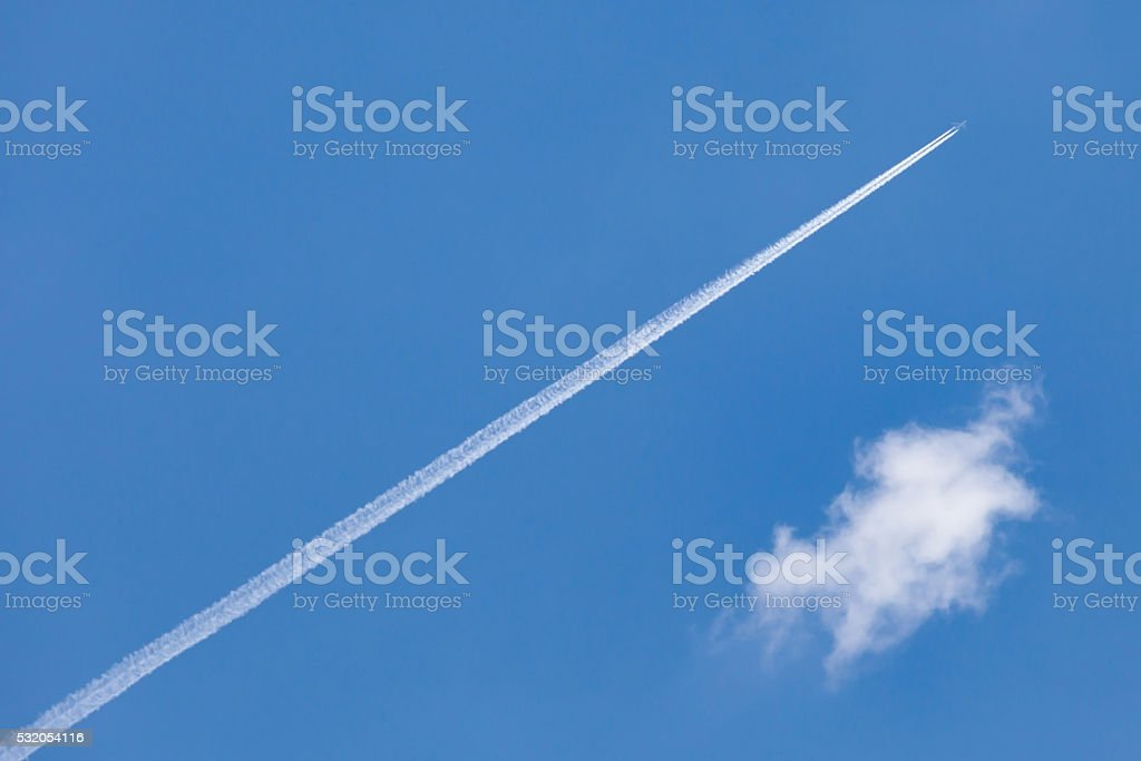 The airplane trail speed through cleared blue sky. stock photo