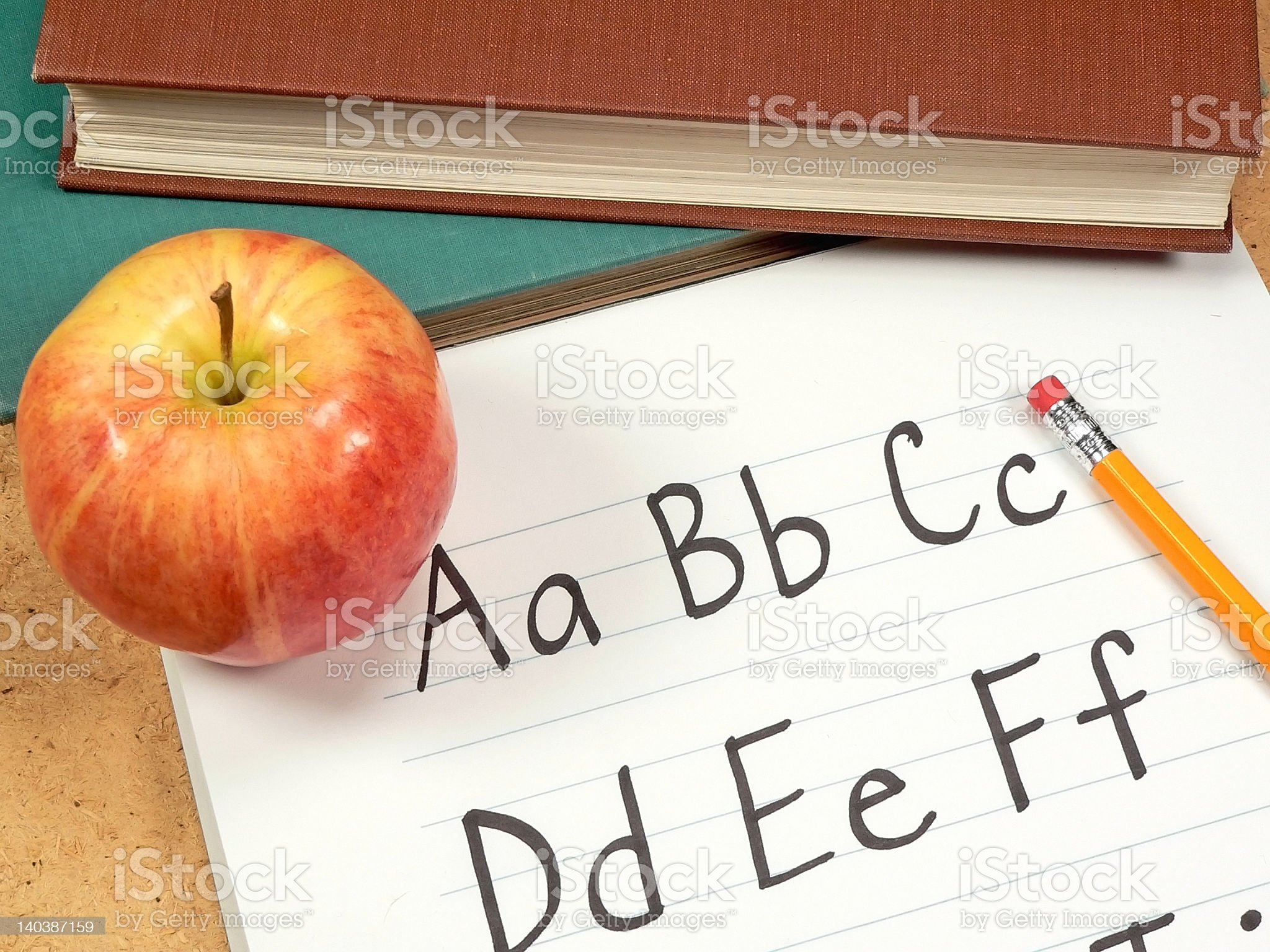 The alphabet written on a notebook with an apple royalty-free stock photo