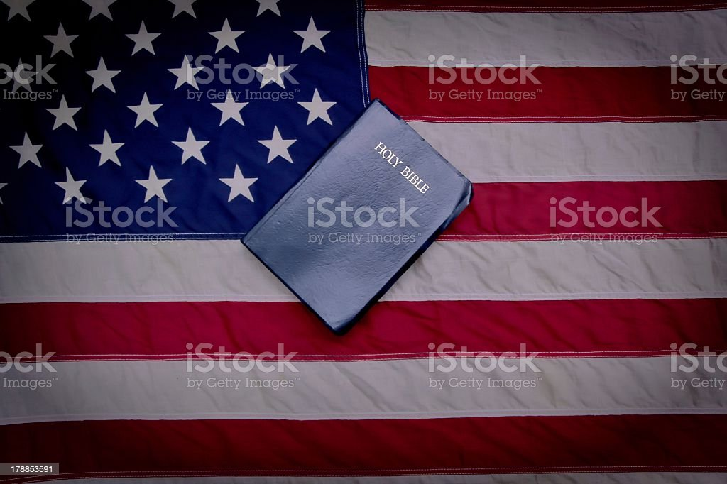 The American flag with a bible sitting on top of it stock photo