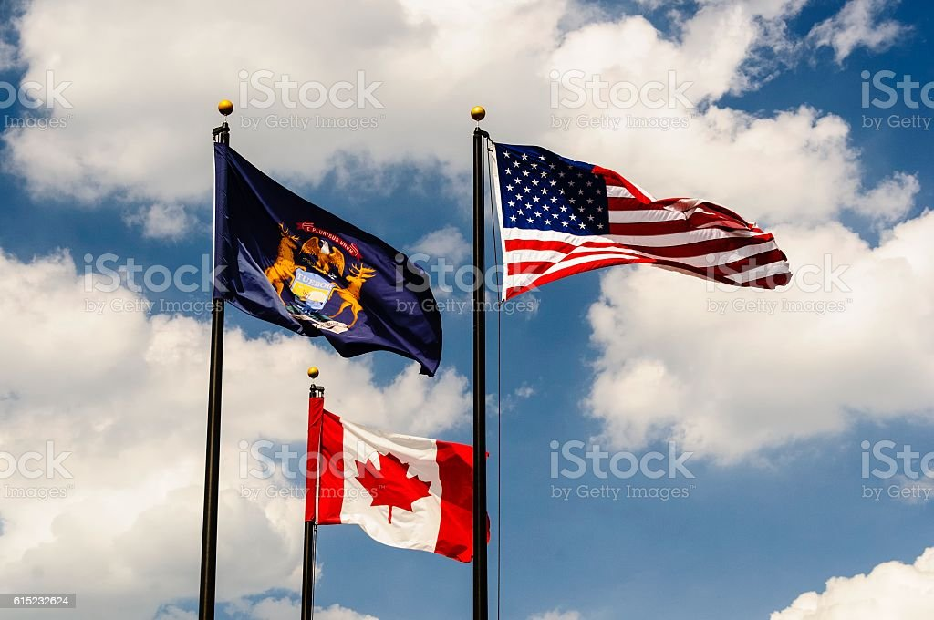 The American, Michigan, and Canadian Flags stock photo