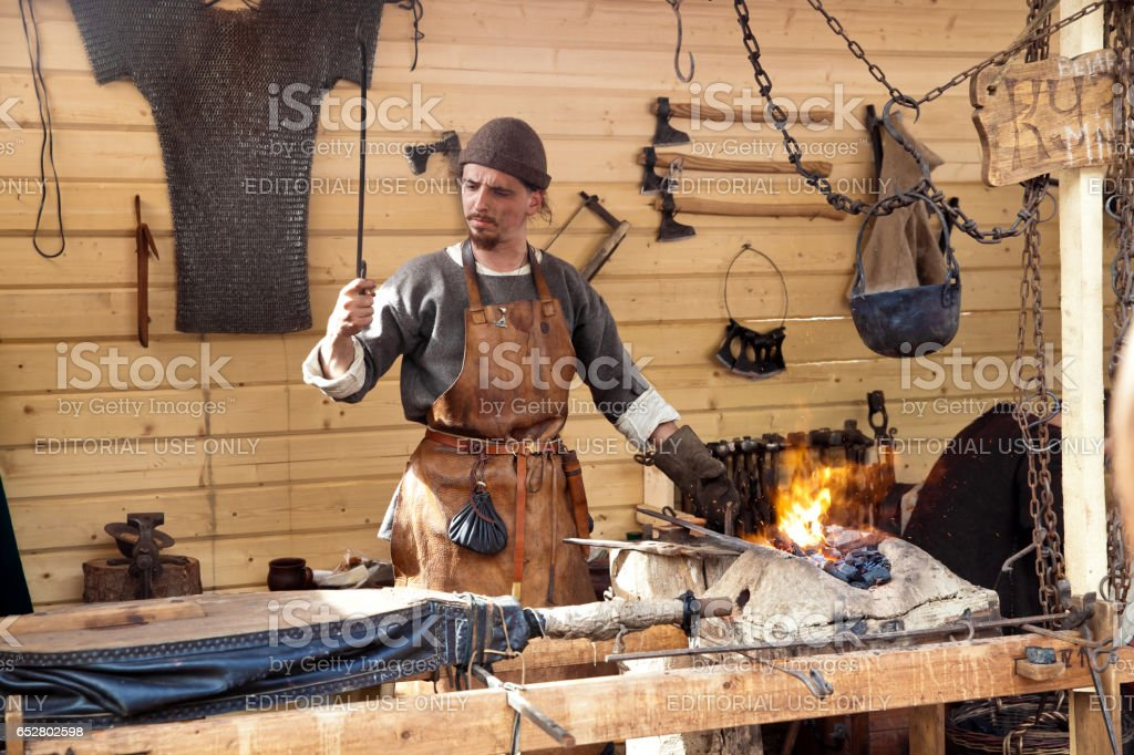 The annual festival in Kolomenskoye. Reconstruction of Ancient Rus. Blacksmith blows the bellows stock photo