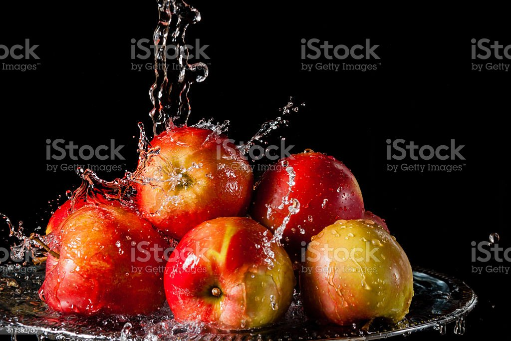 The apples lying on a silver top and falling water stock photo