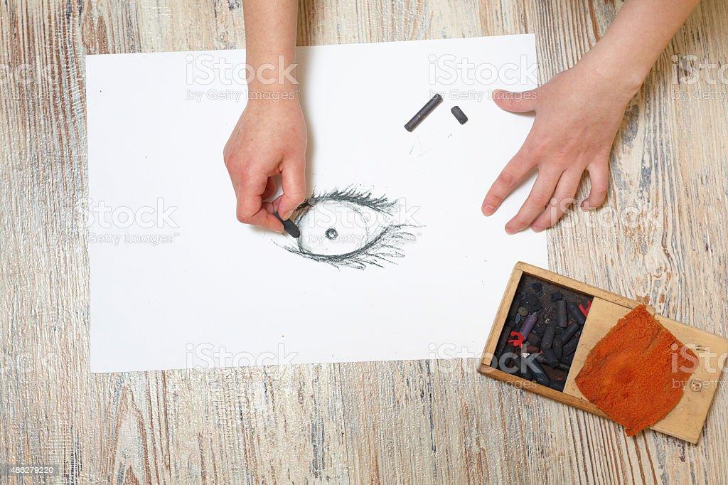 The artist draws the eye of coal. stock photo