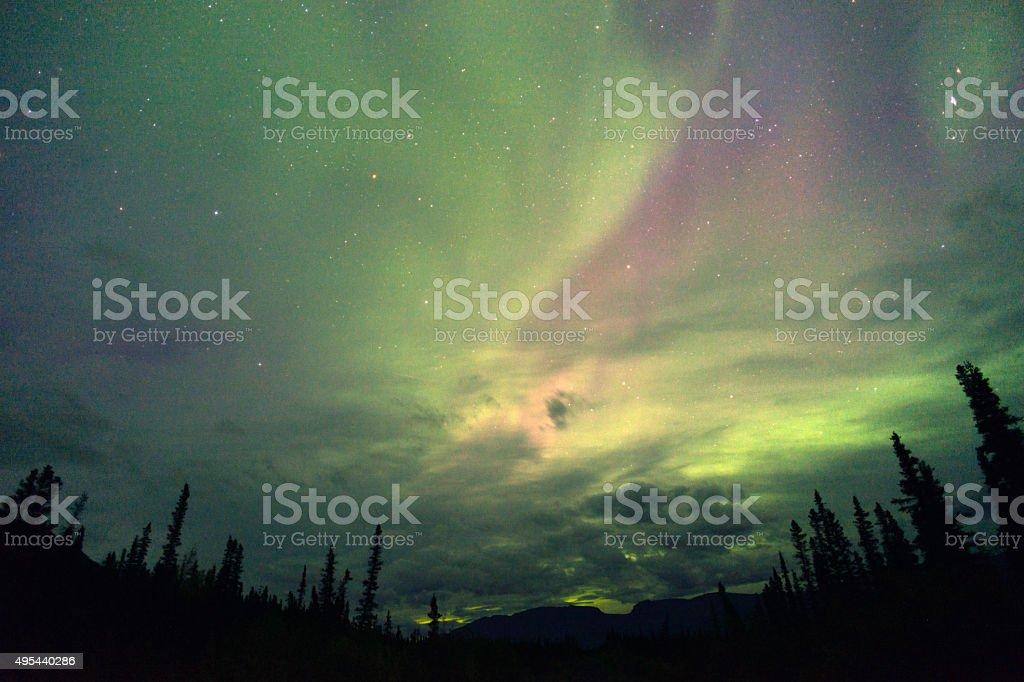 The Aurora Borealis emerge through the clouds in remote Alaska stock photo