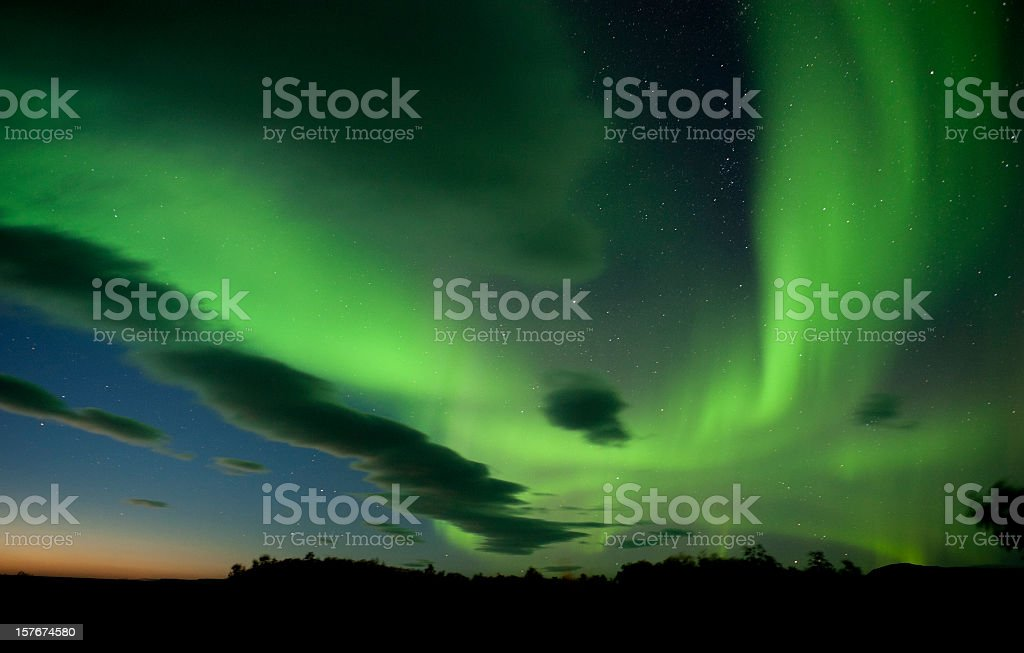 The aurora borealis paints the  night sky with green stock photo