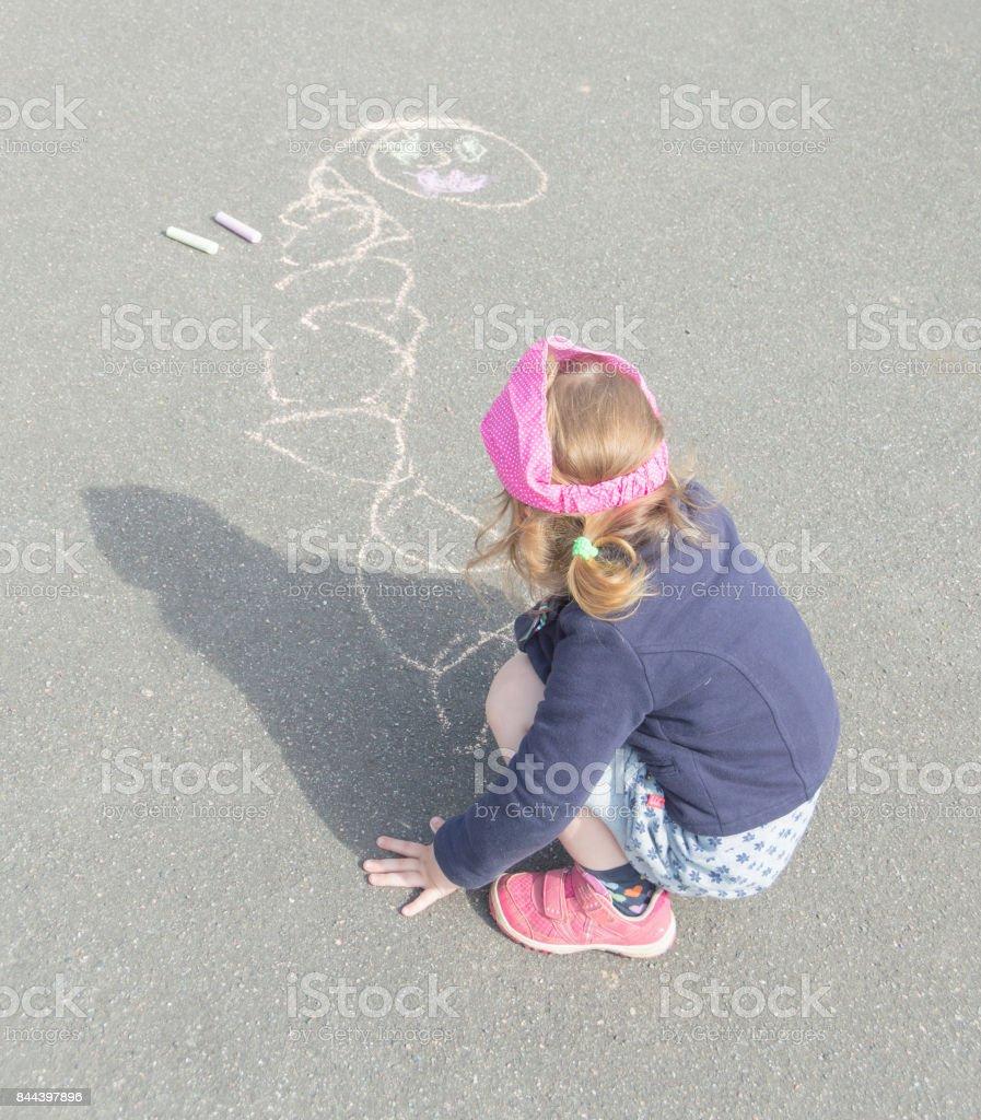 summer day on asphalt with chalk draws a baby girl.