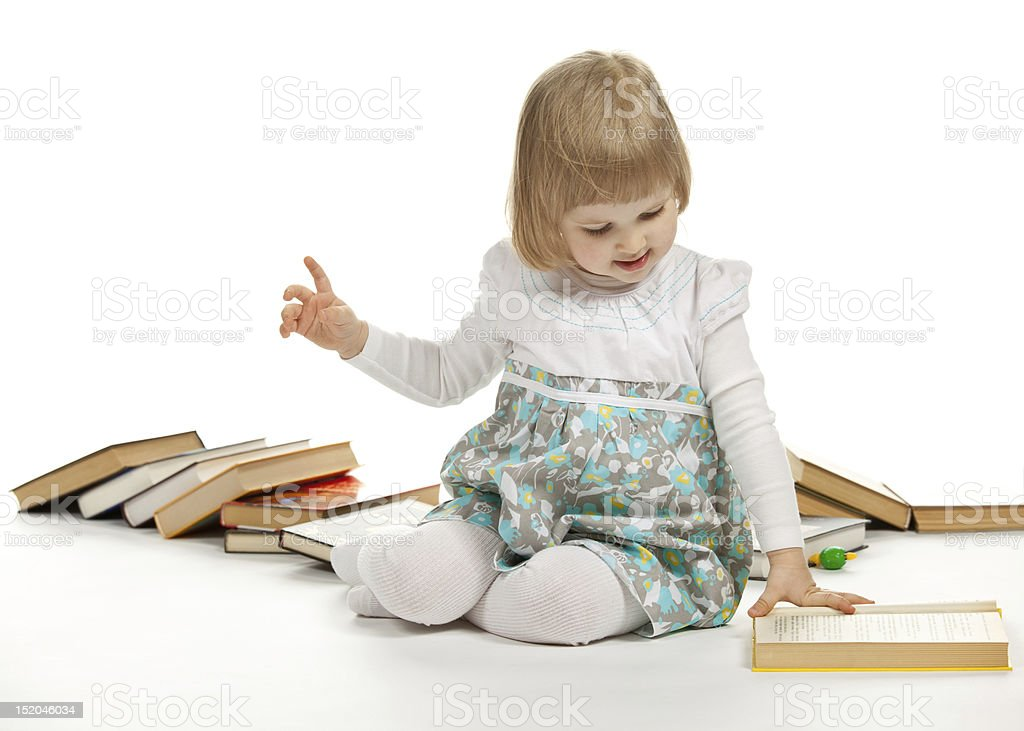 The baby girl sitting among books royalty-free stock photo