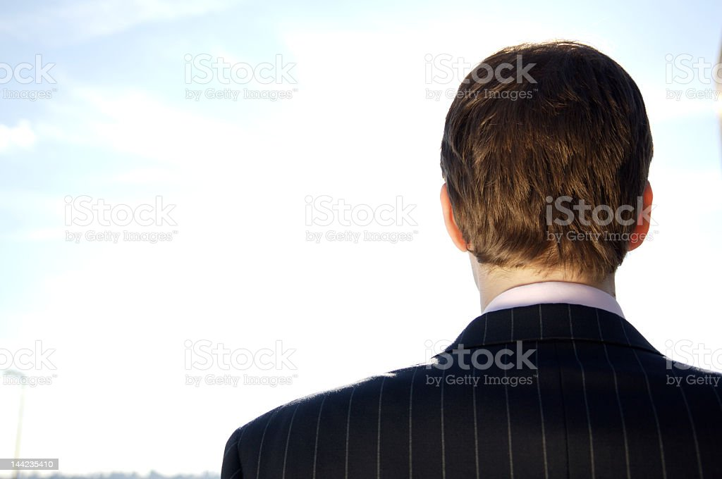 The back side of a businessman in a striped black suit stock photo