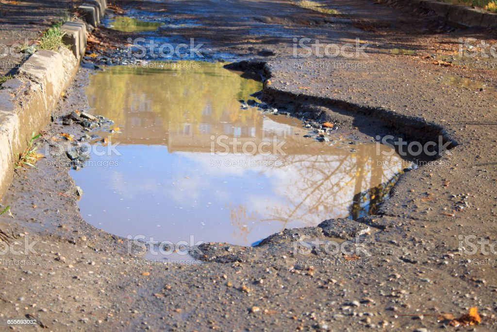 The bad asphalted road with a big pothole. stock photo