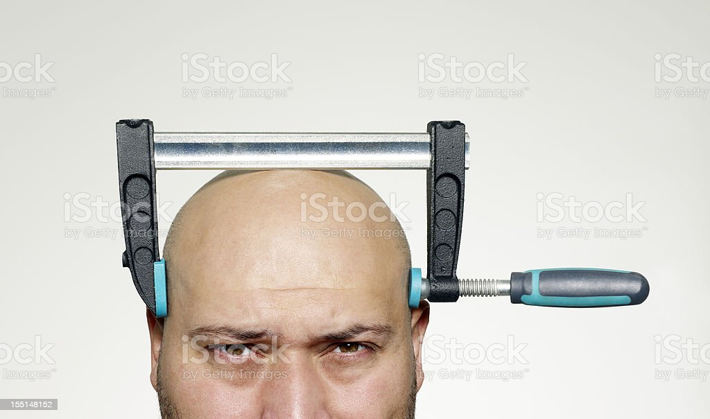 The bald man head with screw clamp compressed stock photo