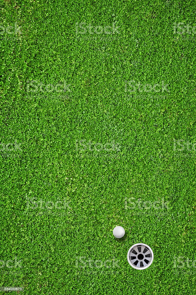 The ball at the hole on the golf course stock photo