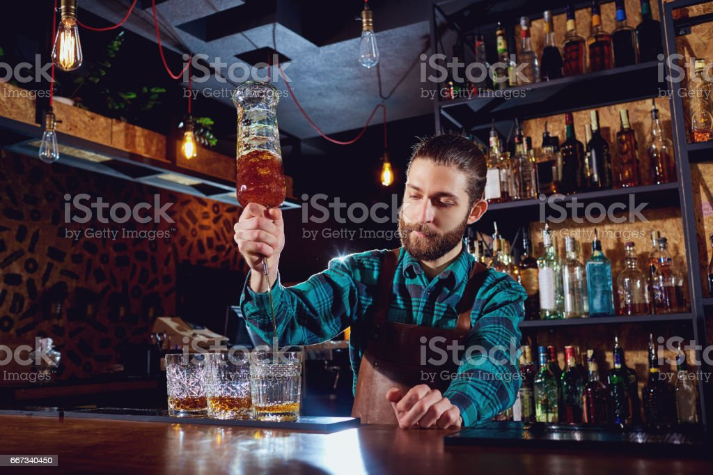 The barman pours alcohol into a glass stock photo