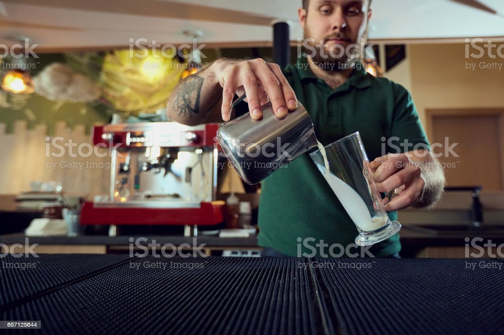 The bartender barista pours  hot milk into a glass in  bar cafe stock photo