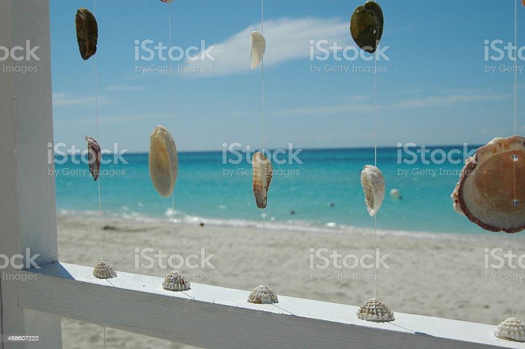 The beach through seashell curtain stock photo