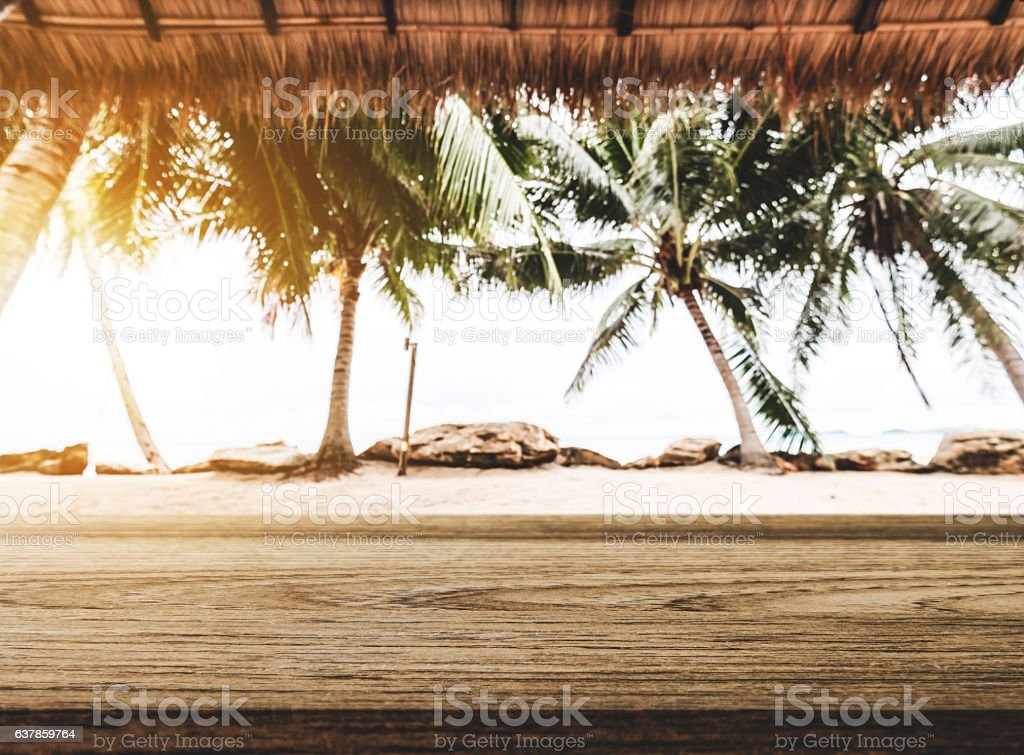 The beach, wooden tabletop with straw roof at tropical beach stock photo