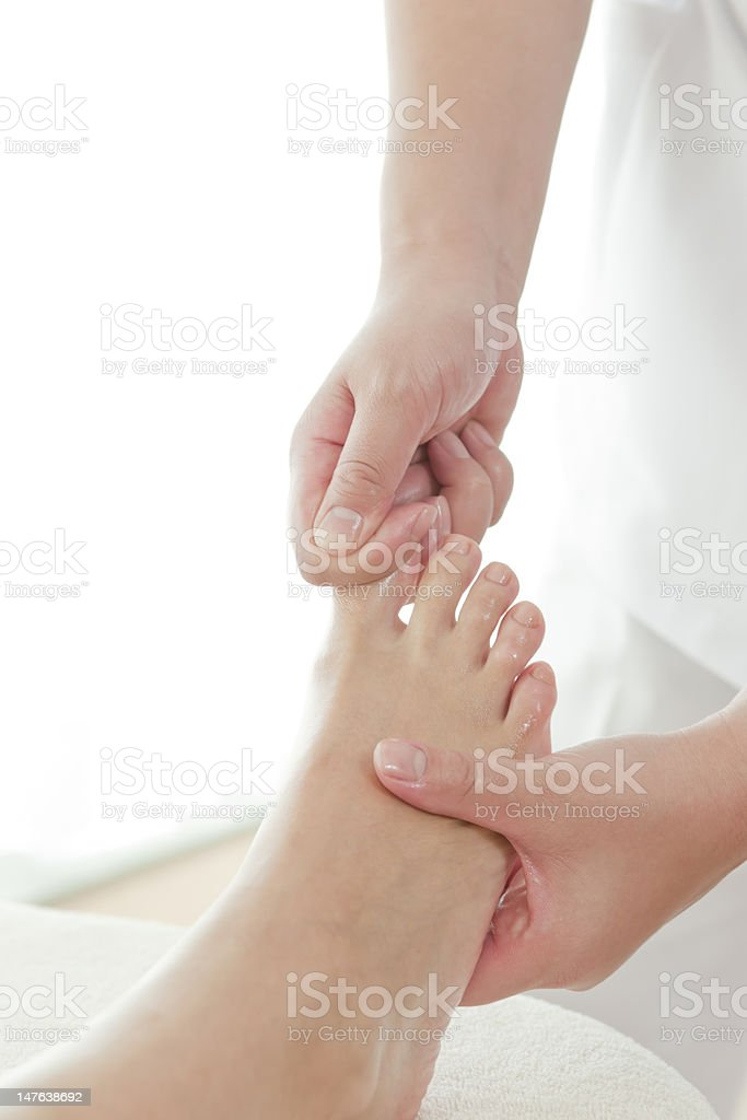 The beautician who massages a foot royalty-free stock photo