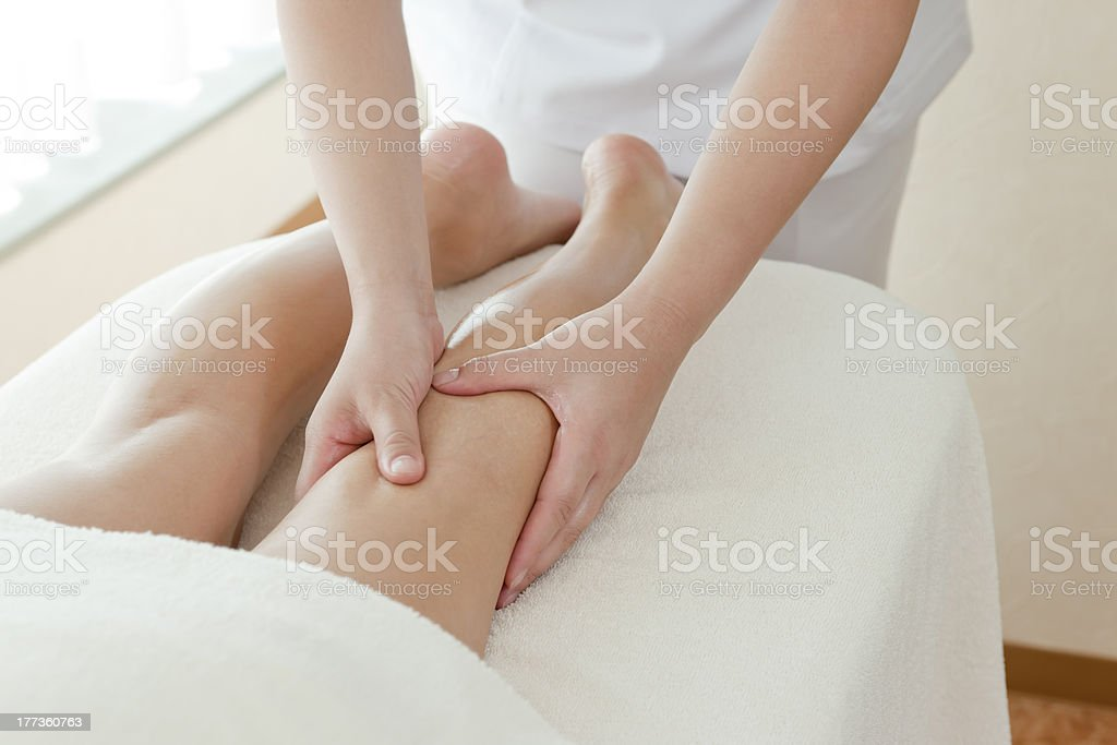 The beautician who massages a leg royalty-free stock photo
