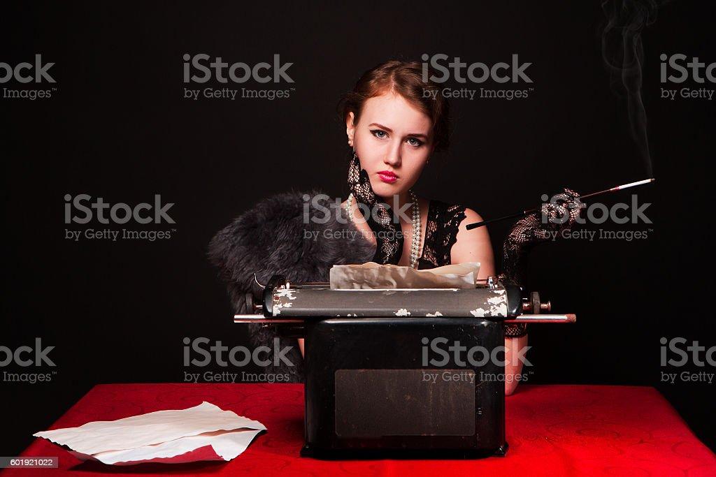 The beautiful girl at a typewriter. Retro stock photo