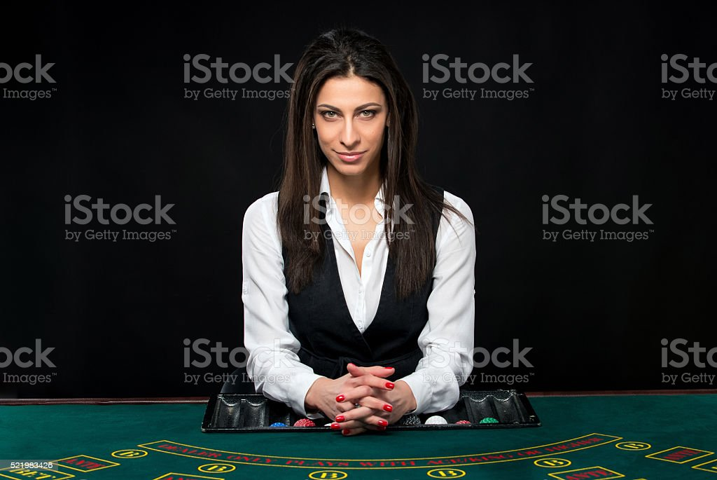 The beautiful girl, dealer, behind a table for poker stock photo