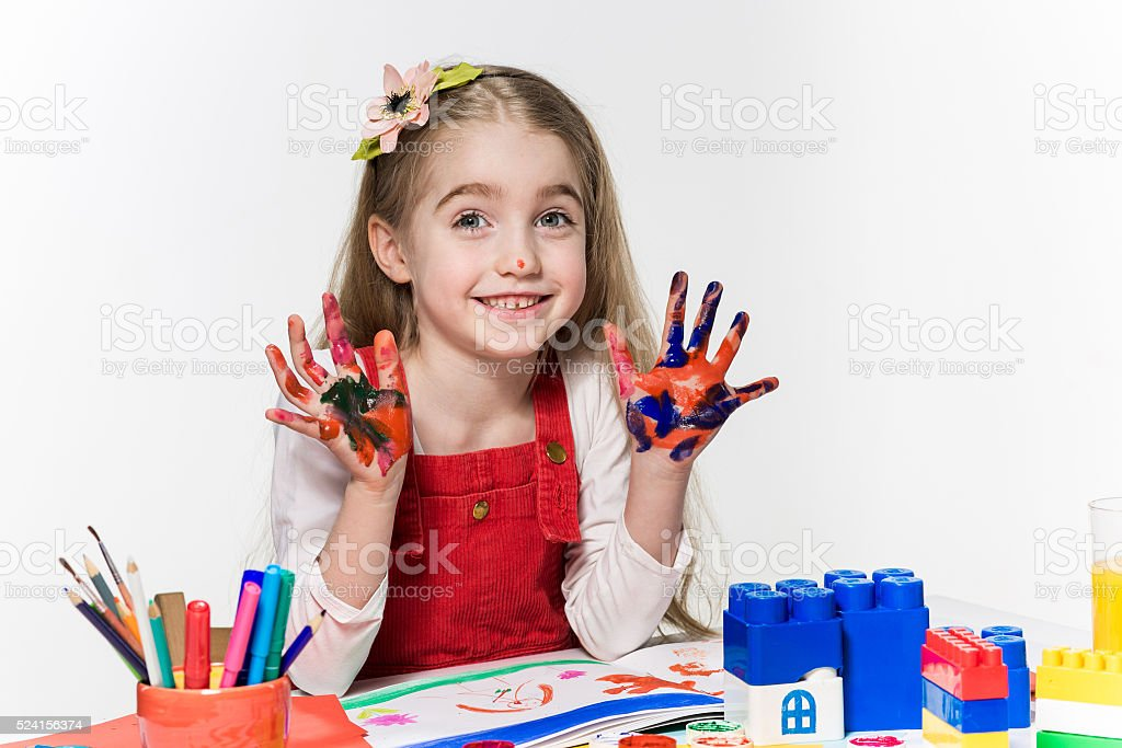 The beautiful little girl with hands in the paint stock photo