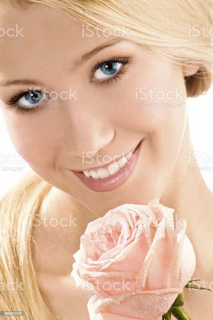 The beautiful lovely blonde with blue eyes and rose. royalty-free stock photo