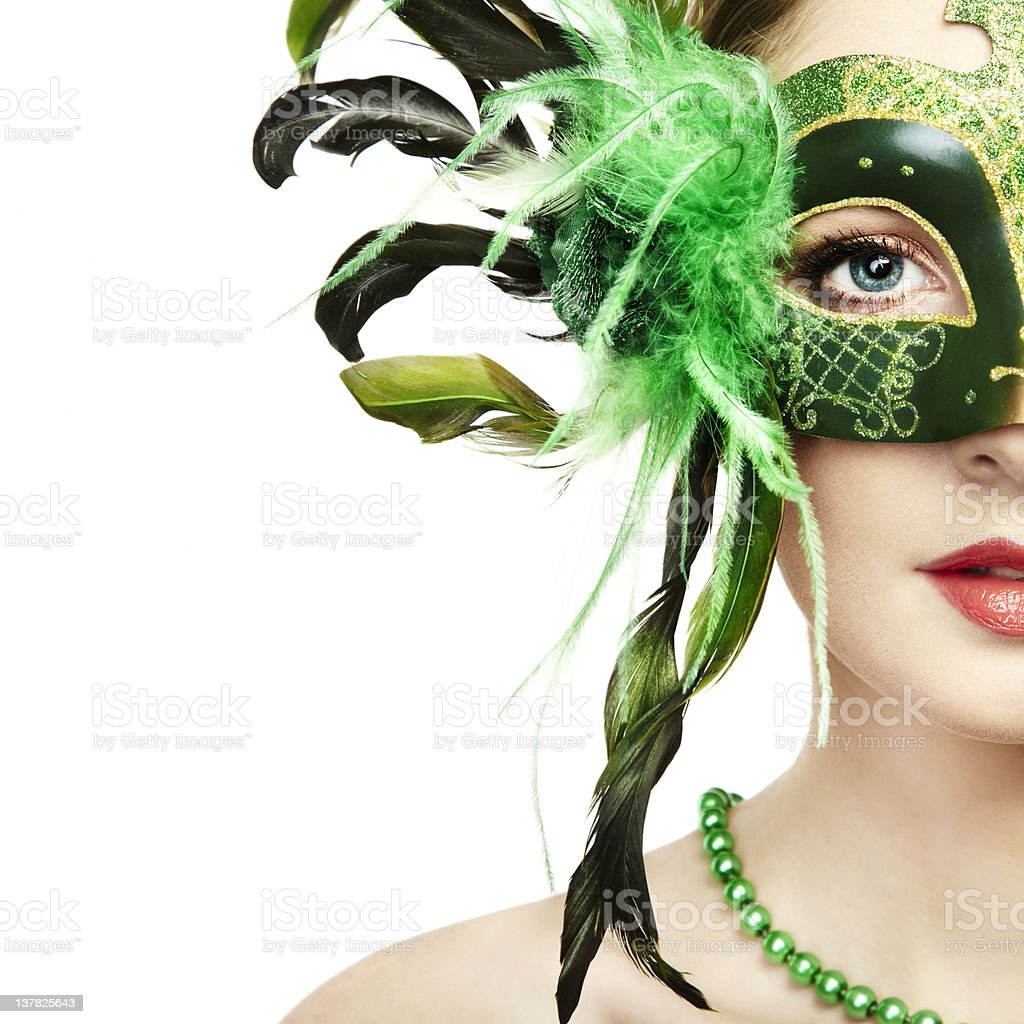 The beautiful young woman in a green venetian mask stock photo