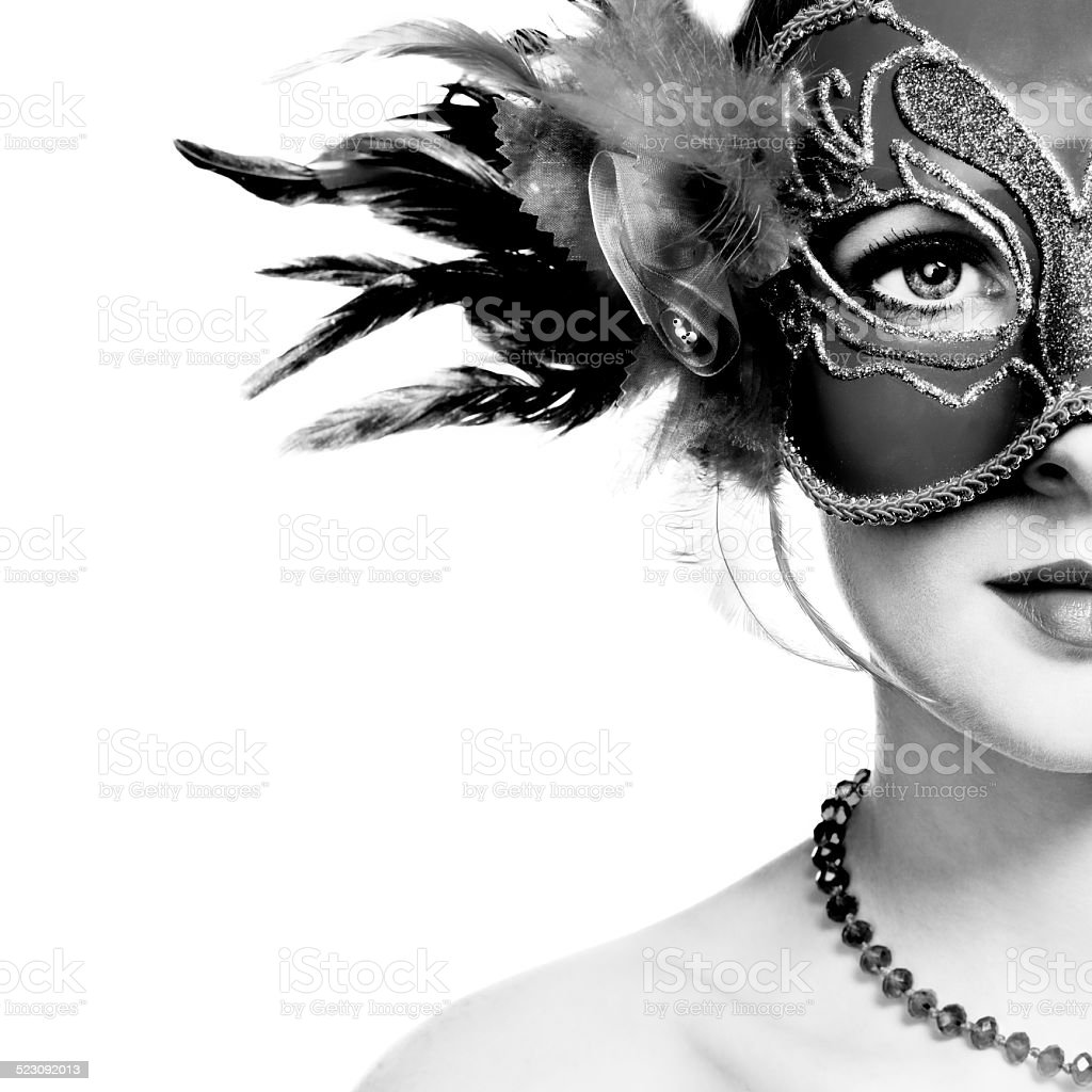 The beautiful young woman in mysterious venetian mask stock photo