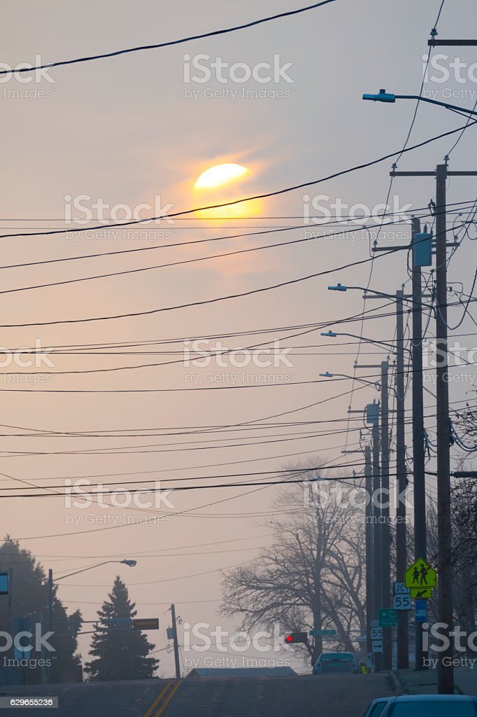 The beauty of sunrise seen through ugly city power lines stock photo