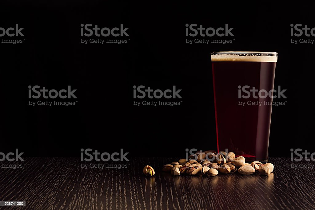 The beer red ale with snacks on a dark background. stock photo