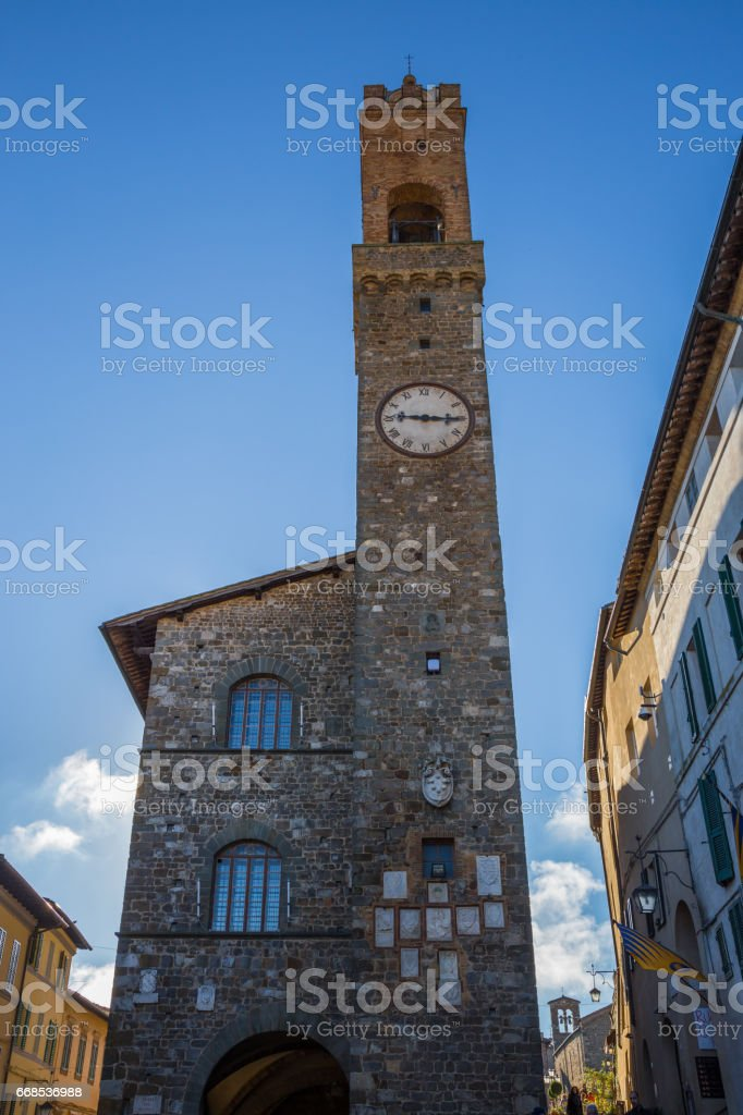 The bell tower over the Palazzo dei Priori in Montalcino in Tuscany in Italy. stock photo