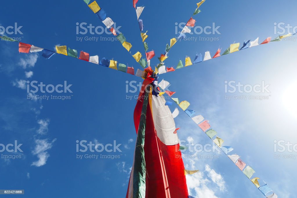 The Bhuddhist Mantra flags from roof top of monastery on blue sky stock photo