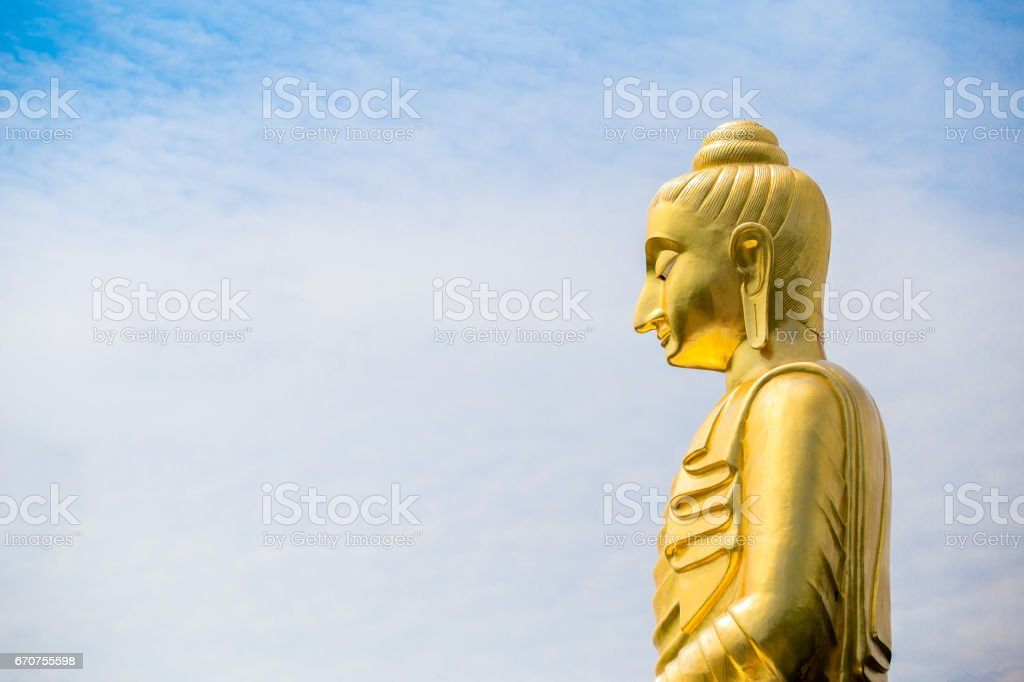 The big Buddha statue against cloudy and blue sky background. stock photo