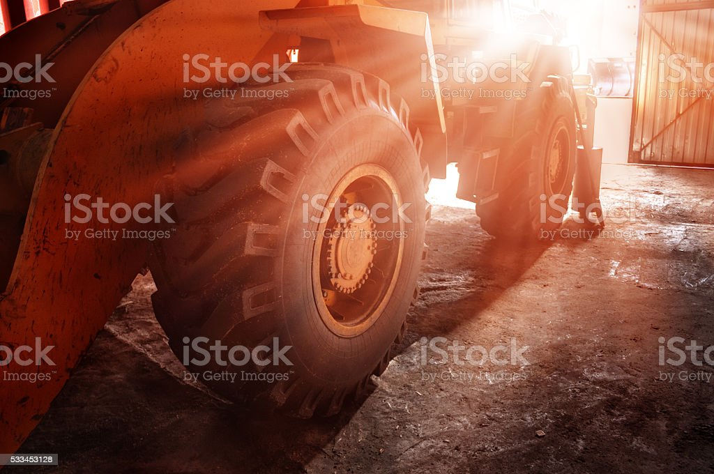 The big yellow wheel of heavy tractor stock photo