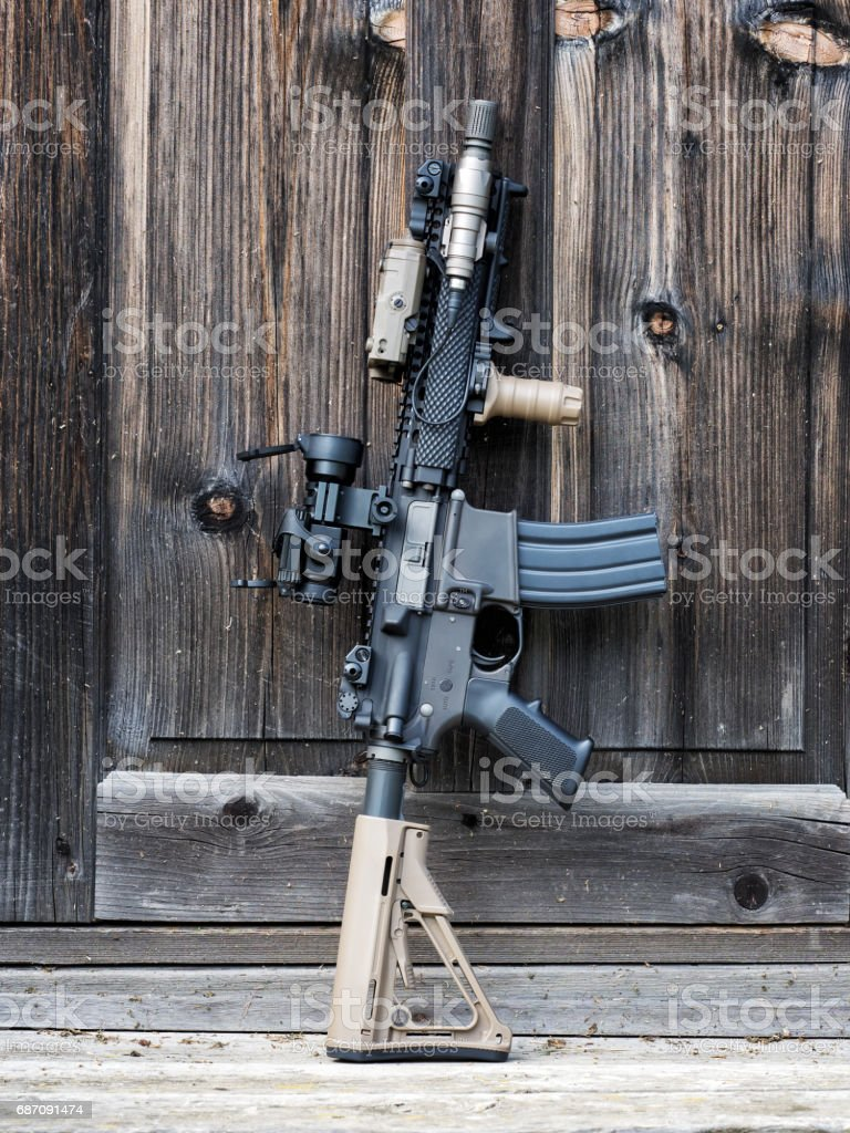 The Black Rifle. Tactical carbine beside wooden door of old house. stock photo