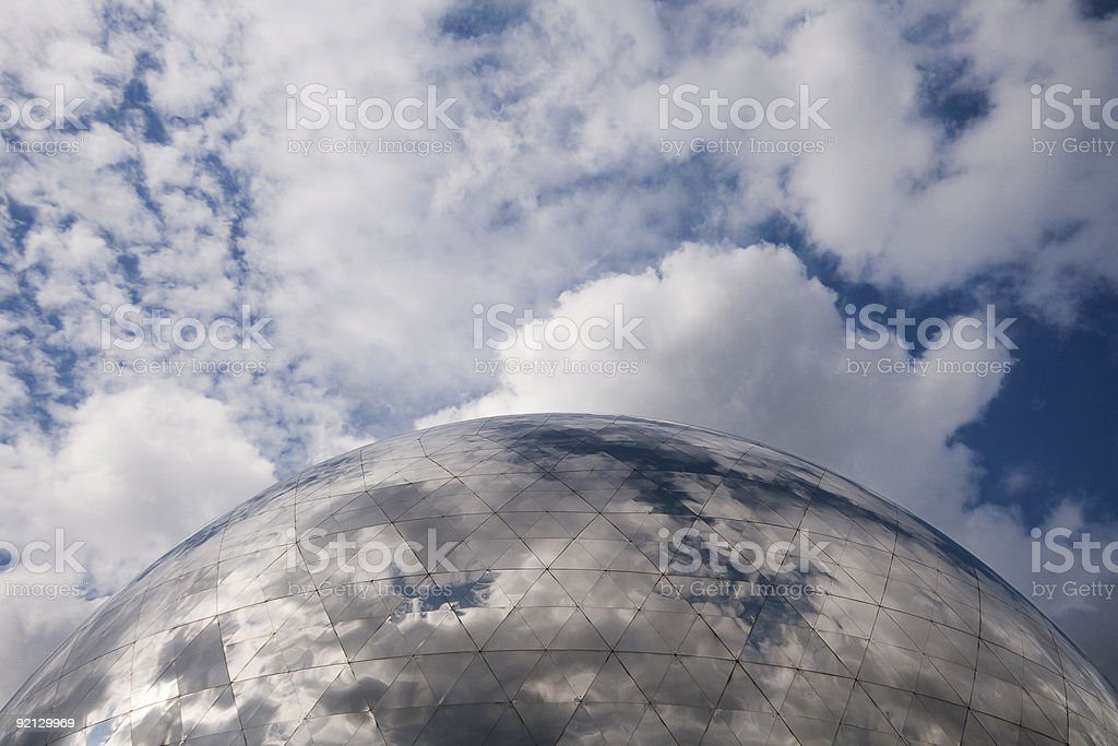 The blue cloudy sky above a marble globe stock photo