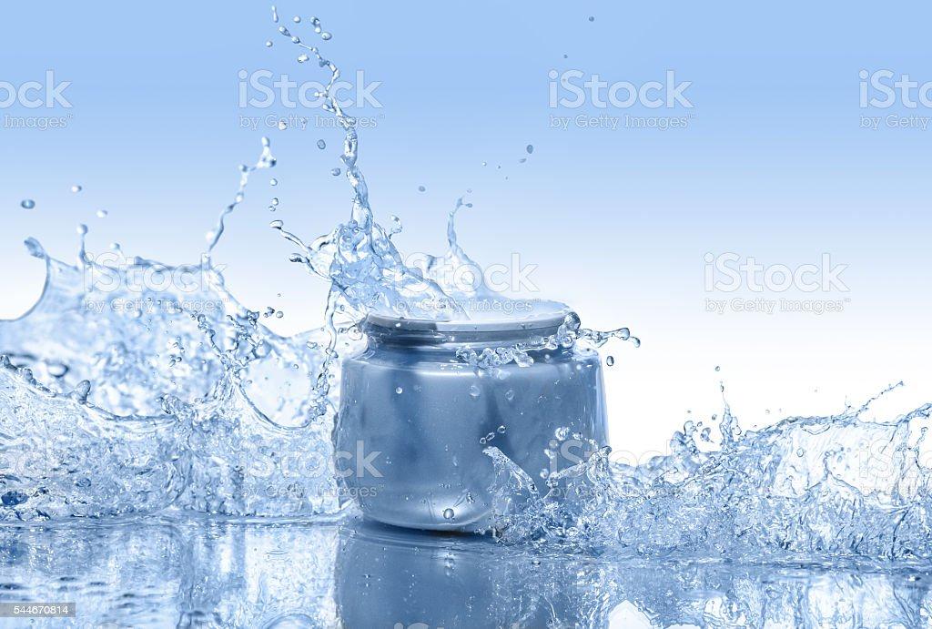 The blue jar of moisturizing cream in the big water splashes stock photo