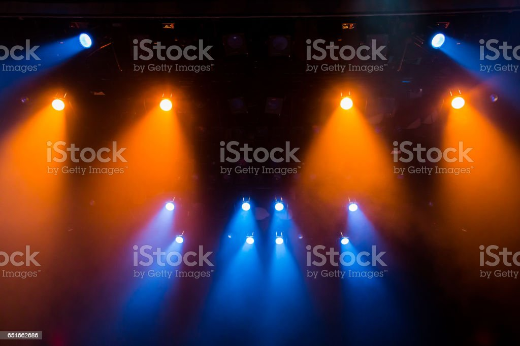 The blue-orange light from the spotlights through the smoke in the theatre during the performance. Lighting equipment stock photo