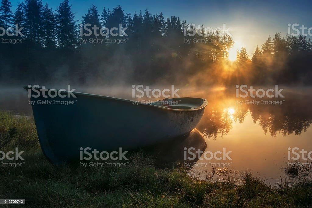 The boat in mountain lake on sunrise stock photo