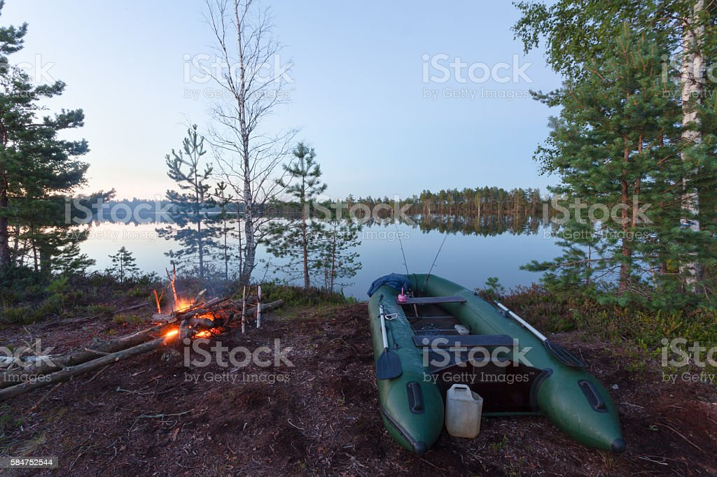 The boat with two spinning on the lake and bonfire stock photo