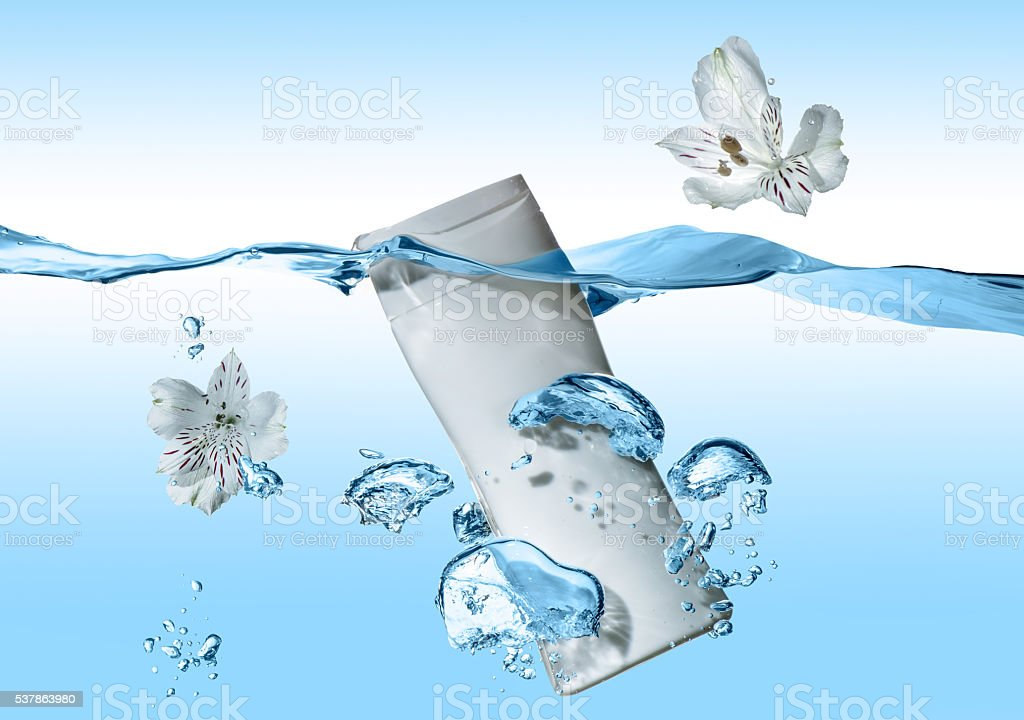 The bottle of cosmetic milk in blue water wave stock photo
