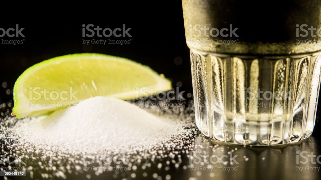 The bottom of a tequila with salt and lime stock photo