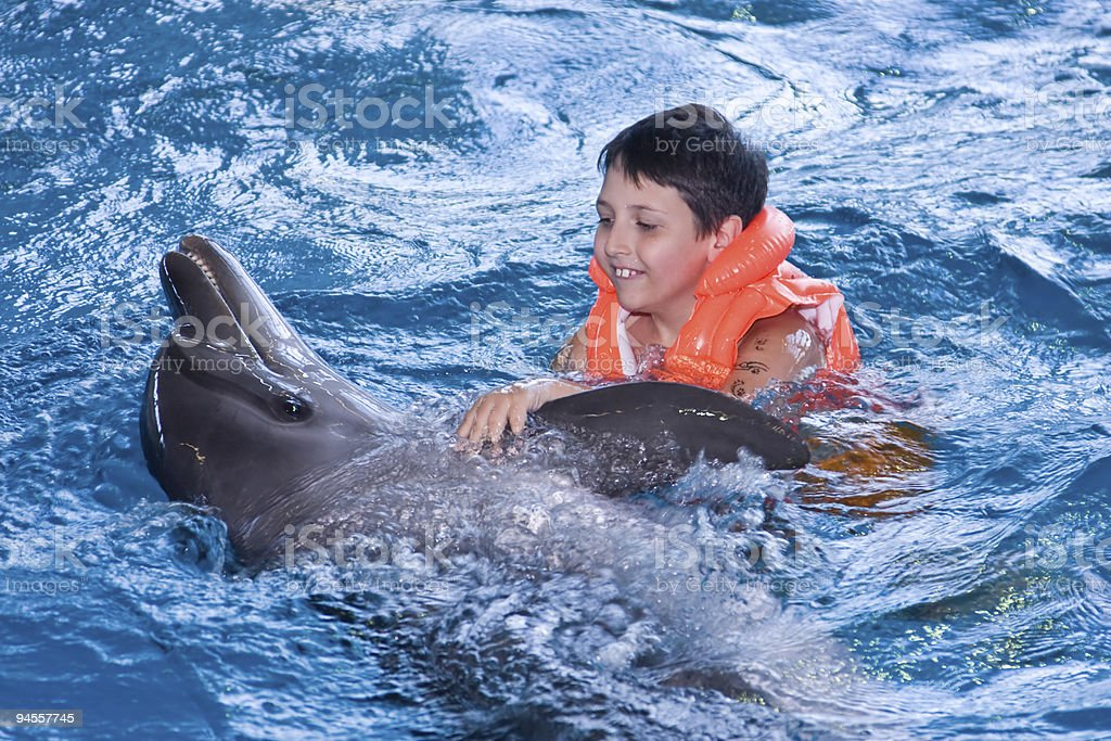 The boy floats in water with a dolphin stock photo