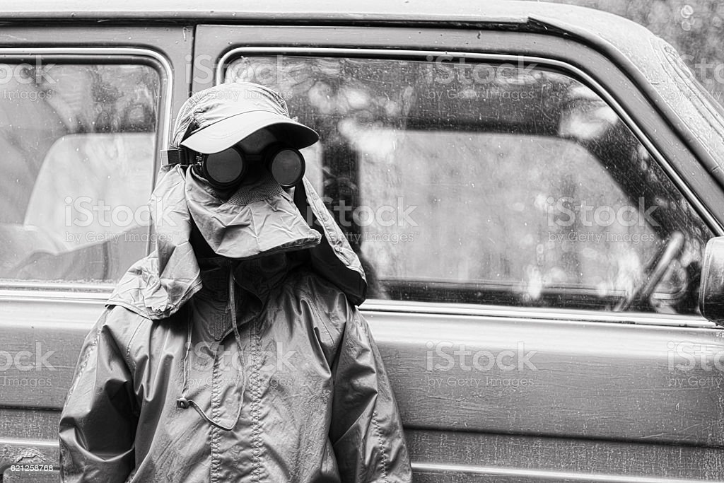The boy in a protective suit stands near a car stock photo